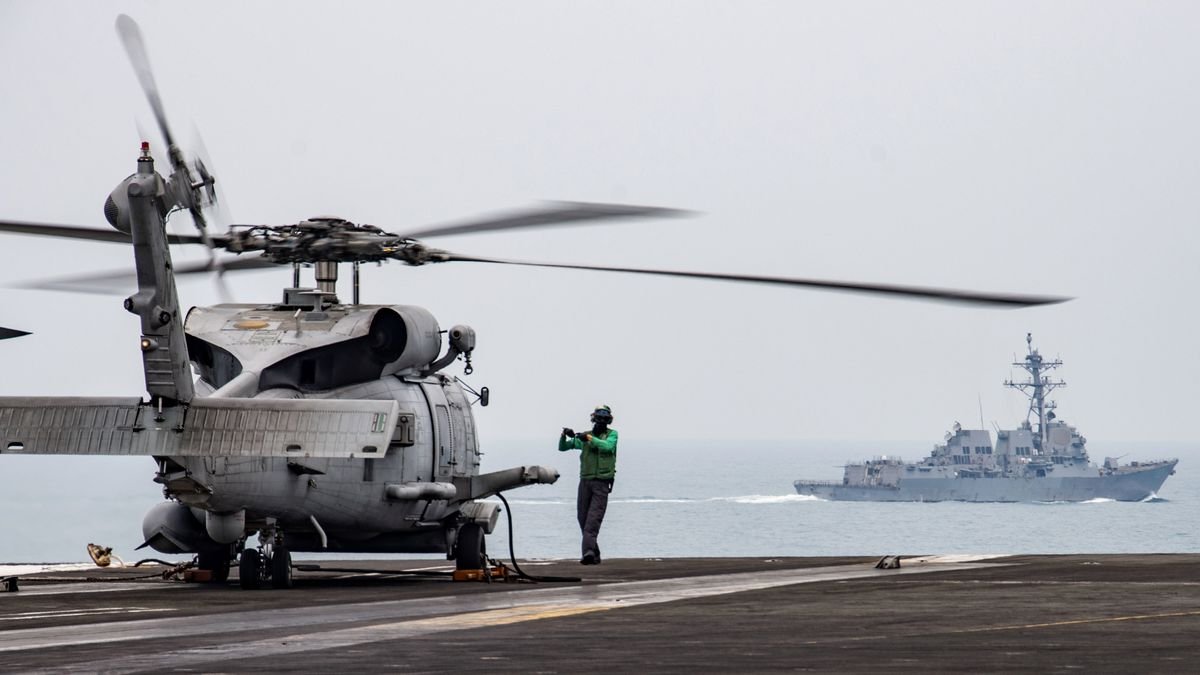 In this photo provided by the U.S. Navy, Aviation Electronics Technician 3rd Class James Benzel, from Louisville, Ohio, assigned to the Saberhawks of Helicopter Maritime Strike Squadron, signals an MH-60R Sea Hawk to disengage its rotors on the flight deck of the USS Ronald Reagan (CVN 76) as USS Mustin (DDG 89) steams alongside in the South China Sea, Thursday, July 9, 2020.