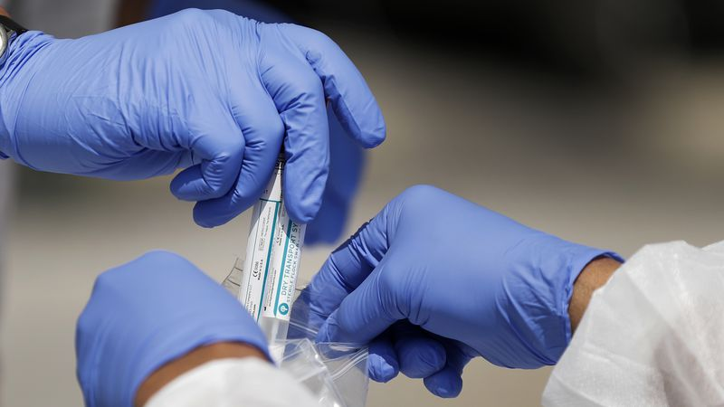 FILE - In this April 16, 2020, file photo, vials containing nasal swabs collected at a COVID-19...