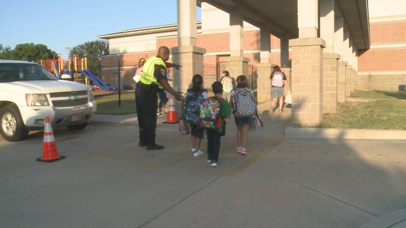 A police officer guides kids across the crosswalk at Lincoln Elementary in Ardmore.