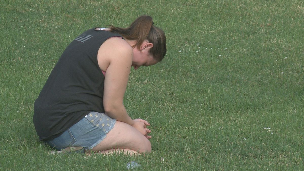 A woman kneels at the silent prayer event in Ardmore Tuesday evening.