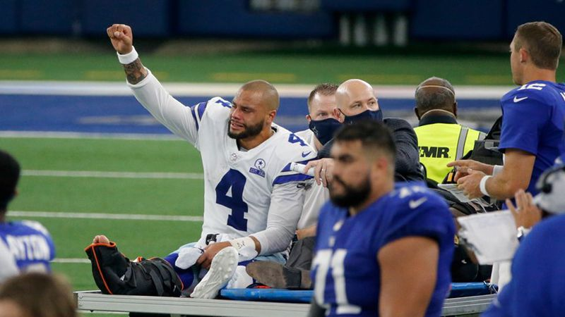 Dallas Cowboys quarterback Dak Prescott (4) lifts his fist to cheers from fans as he is carted...