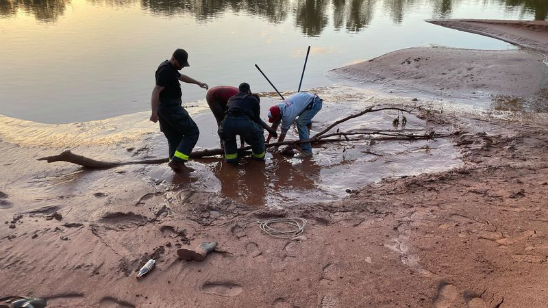 Tishomingo firefighters work to rescue a boy stuck in quicksand at the Washita River Wednesday...