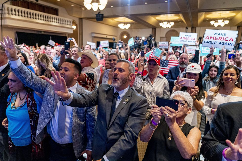 Supporters react as President Donald Trump speaks at a Latinos for Trump Coalition roundtable at Arizona Grand Resort & Spa, Monday, Sept. 14, 2020, in Phoenix.
