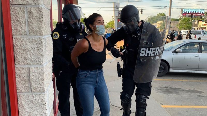 Police officers are shown arresting Des Moines Register reporter Andrea Sahouri after a Black...
