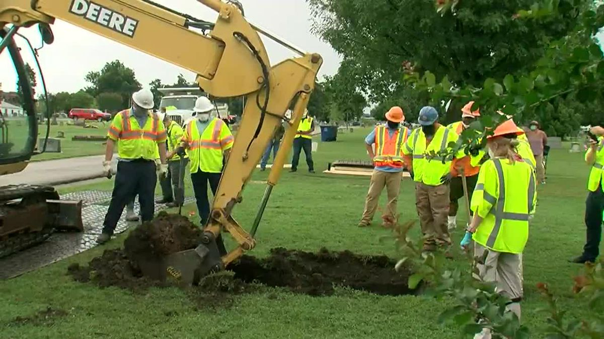A backhoe is being used to dig down as part of an excavation searching for race massacre...